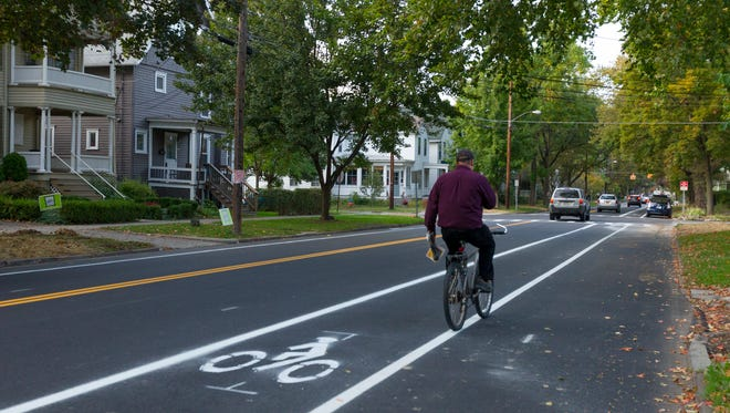 A cyclist heads north on Cayuga Street about 6 p.m. Thursday after bike lanes were marked out on the street. There are bike lanes in both directions, with parking only on the east side, against the curb.