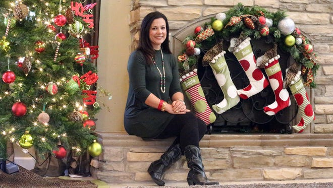 Nichole Ayoub Hughes sits by the fireplace of her Upper Valley home decorated for the Christmas holiday season. The home will be one of five featured in the El Paso Pro-Musica Guild Holiday Tour of Homes.