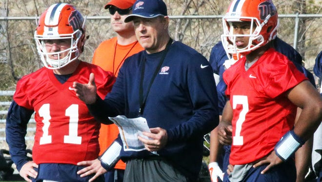 Brent Pease, center, new UTEP offensive coordinator and quarterbacks coach talks with quarterbacks Mack Leftwich, left, and Kavika Johnson, 7, during the team's first day of spring practice Monday at Glory Field.