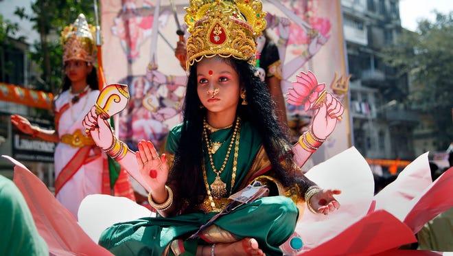 "A young Indian girl dressed as Hindu goddess Laxmi participates in a procession to mark ""Gudi Padwa,"" or Maharashtrian New Year, in Mumbai, in the Indian state of Maharashtra, Friday, April 8, 2016. (AP Photo/Rajanish Kakade)"