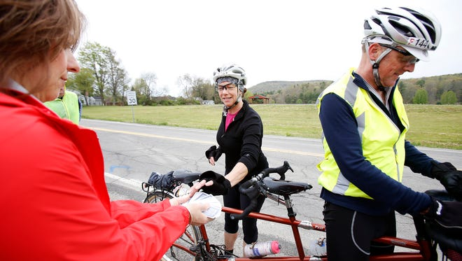 Wanda Kingsbury selects a card from Meals on Wheels board member Angela Cavaluzzi Saturday at a Poker Ride stop in Big Flats near the intersection of Sing Sing Road and Chamber Road. She rode a tandem bike with her husband, Paul, on the 24-mile course.