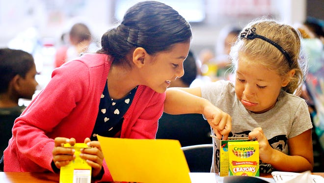 Students Giselle Garcia, 7, left, and McKenzie Goheen, 7, choose a color while decorating their passport project in ESL (English as a Second Language) summer camp at Dallastown Middle School in Dallastown, Thursday, June 23, 2016. Dawn J. Sagert photo