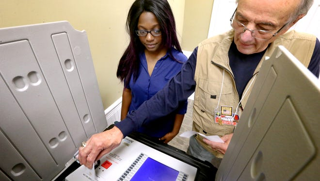 Poll worker Hooper Penuel, right gets the machine ready for Jenice Mells to vote at the Middle Tennessee Association of Realtors, on the last day of early voting, Thursday, Nov. 3, 2016.
