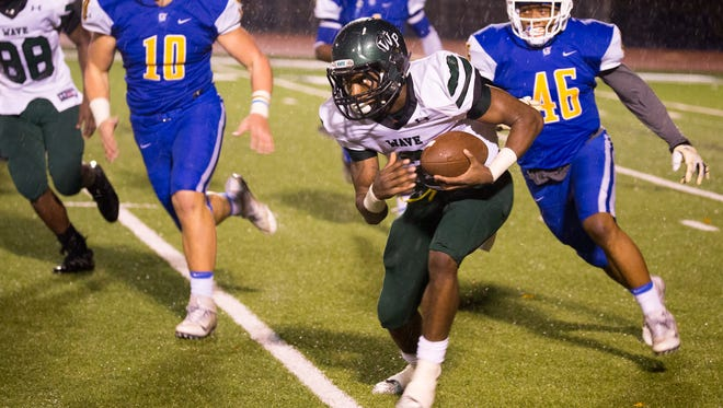 West Point's Marcus Murphy evades Oxford defenders in a playoff game.