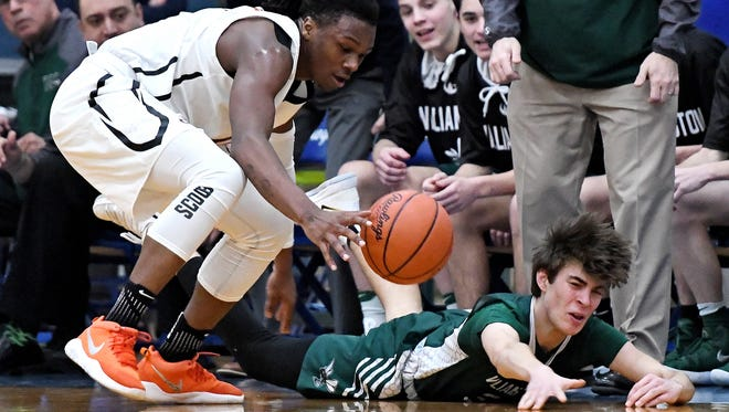 Williamston's Case Conley, right, and Benton Harbor's Carlos Johnson go for a loose ball during the second quarter on Tuesday, March 20, 2018, at Ionia High School.
