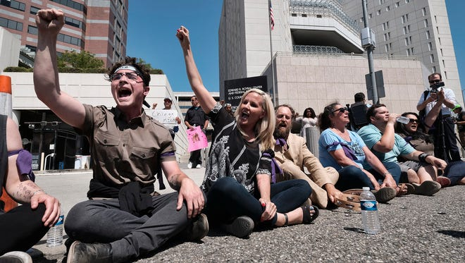 Protesters chant slogans and stage a sit-in before being arrested in front of the Immigration and Customs Enforcement facility in downtown Los Angeles on July 2, 2018.