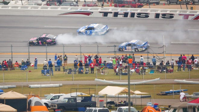 Jamie McMurray, left, blows an engine as fans in the infield look on at Talladega Superspeedway.