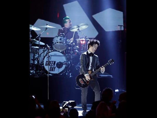 Billie Joe Armstrong, front, and drummer Tre Cool, of Green Day, perform at the Rock and Roll Hall of Fame Induction Ceremony Saturday, April 18, 2015, in Cleveland. (AP Photo/Mark Duncan)