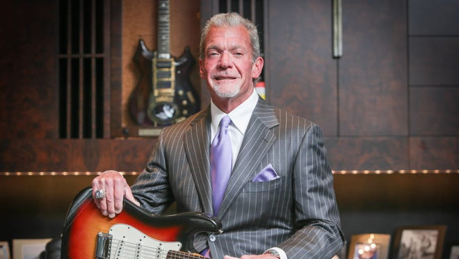 """Tuesday June 10th, 2014, Indianapolis Colts owner and CEO Jim Irsay, holds the Fender Stratocaster  played by Bob Dylan at the Newport Folk Festival, where he first went electric. Irsay, shown here in his office, at the Indiana Farm Bureau Football Center, paid one million dollars for the guitar. In the case behind is Jerry Garcia's guitar, """"Tiger"""", his main guitar between 1979 to 1989."""
