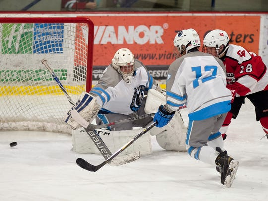 Champlain Valley's Quinn Francis, right, tucks a goal past South Burlington netminder Logan Riddle during Saturday's CSB Cup boys hockey game at Cairns Arena in South Burlington.