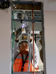 Gwen Jim of DKD Electric works on the fourth floor of San Juan Regional Medical Center on Feb. 10 in Farmington.
