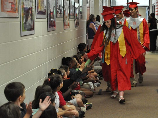 Graduating Pineville High School seniors led by Anna White walk through the halls of J.I. Barron Sr. Elementary School in cap and gown Monday.