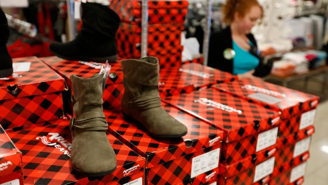 Selling associate Emily Toulouse (back right) removes some of the excess packaging from boxes of new boots Thursday, Nov. 19, 2015, a top seller during Black Friday, at the Valley West Mall JC Penny in West Des Moines.