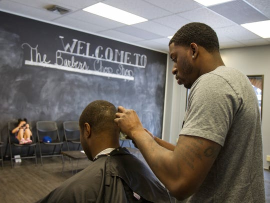 Marvin Newkirt finishes up a haircut for Darius Hammons