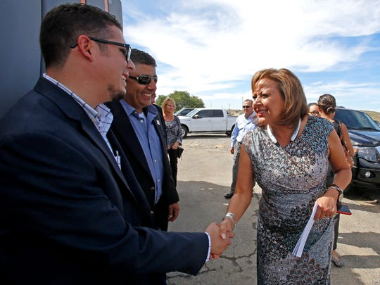 Marcos Trujillo, left, policy director for the New Mexico Department of Transportation, shakes hands with Gov. Susana Martinez on Tuesday during a press conference in Farmington on funding for improvements along U.S. Highway 64.
