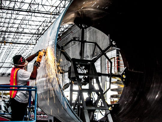 A Hyperloop One employee works on one of the transport