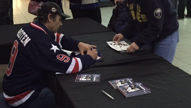 Neal Broten signs autographs before Friday's Amerks game. He later headed to Lake Placid to take part in Saturday's Miracle on Ice 35th anniversary reunion.
