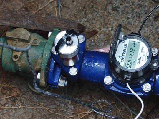 A leak detection logger unit rests on top of a water meter Thursday afternoon in Mountain Home. The loggers listen for ambient noise generated by water escaping under pressure, and indicate to city employees that a potential water leak is nearby.