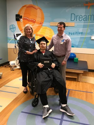 Dr. Adam Nelson, right, and Kathy Ball, left, have been instrumental in the care of Skyler Paris, who graduated from Stewarts Creek Elementary at the Cincinnati Children's Hospital.