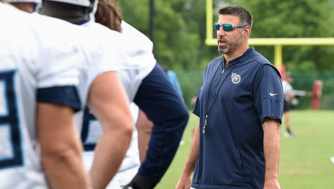 New Titans coach Mike Vrabel talks with his players during practice in June at Saint Thomas Sports Park.