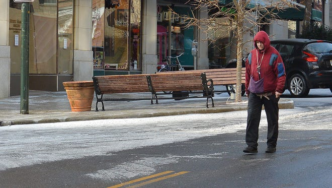 Pedestrians took to city streets to avoid icy roads Tuesday morning in downtown Asheville.