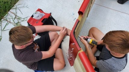 Two Milan boys use drills to help construct the gaga court for Wilson Park.