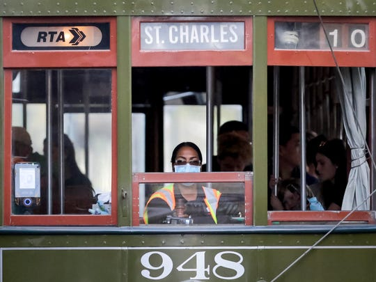 A streetcar conductor wears a mask on St. Charles Avenue in New Orleans on Saturday, amid an outbreak of the new coronavirus.
