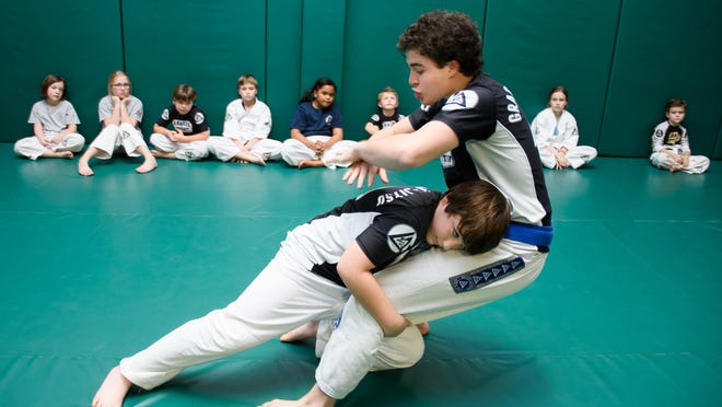 Houston Cottrell, right, owner and lead instructor at Gracie Jiu-Jitsu in Gluckstadt, is pushed to the mat by student Nate Newton to demonstrate a defensive technique for a group of younger students during an evening class recently.