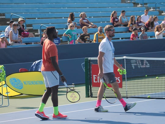 Frances Tiafoe (left in orange) volleyed with several