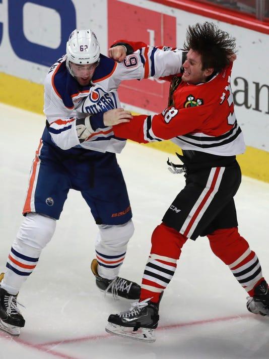 Chicago Blackhawks left wing Ryan Hartman (38) and Edmonton Oilers defenseman Eric Gryba (62) fight during the second period of an NHL hockey game Saturday, Feb. 18, 2017, in Chicago. (AP Photo/Jeff Haynes)