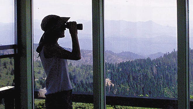 A visitor in the Onion Mountain fire lookout surveys surrounding mountains in the Siskiyou National Forest.