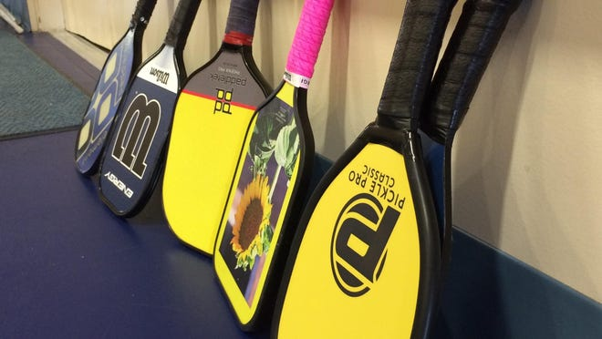 Pickleball paddles are lined up along a wall. The paddle order constitutes whose got the next game.