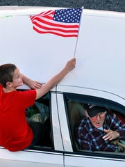 Hagen Gaines, left, of Anderson holds a flag high above his great-great grandfather Ansel Hammonds, Jr, a U.S. Army World War II Pearl Harbor survivor, in a past Anderson County Veterans Parade.