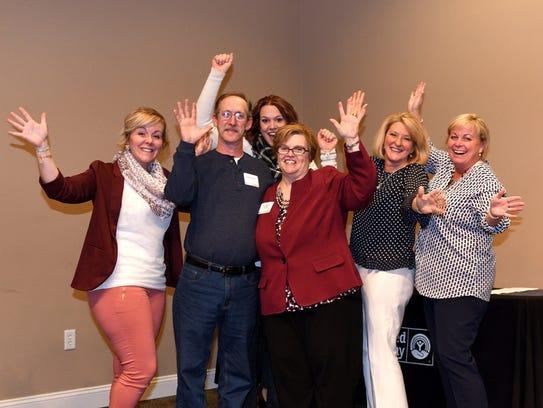 Pam Blantz, at center in the red blazer, celebrates
