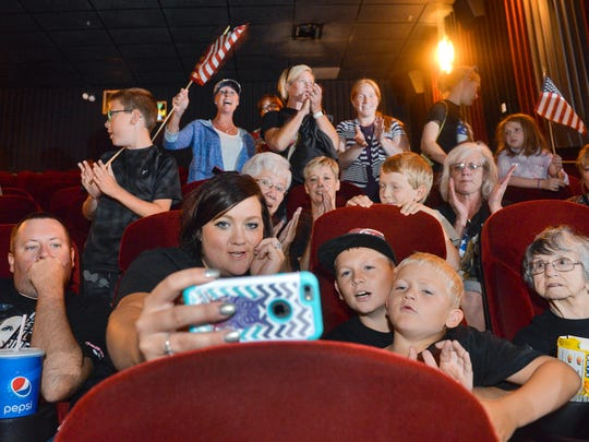 Heather Post, Sauk Rapids, holds her cellphone as she and her husband, Adam, and the rest of the Post family watches Olympic BMX rider Alise Post's finish Friday, Aug. 19, 2016, in the semifinals in Rio. About 150 family members and friends showed up at Marcus Parkwood Cinema to cheer Alise on but there was a technical problem showing the simulcast on the theater screens.