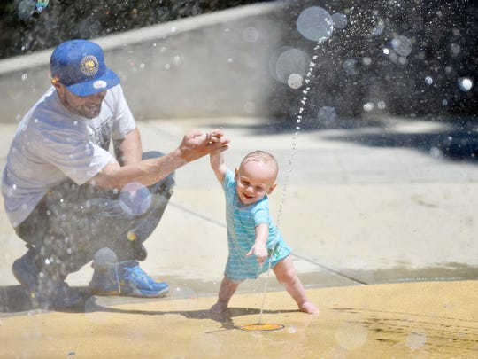 Justin Bucher of Harrisburg plays with his 18-month-old son Jaxon Bucher, of York, at Penn Park's splash pad on Friday in York. The city recently opened the splash pad for the season. Weather permitting, it will be open 11 a.m. to 7 p.m., seven days a week.