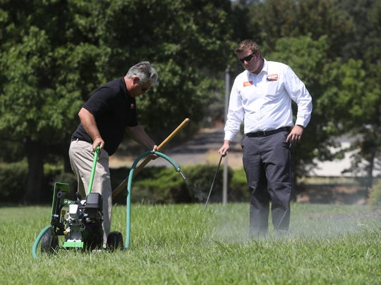 Big Time Pest Control Service Manager Chuck Branscomb, left, and Pest Control Technician Tyler Mair attempt to drive out moles Wednesday in Palo Cedro.