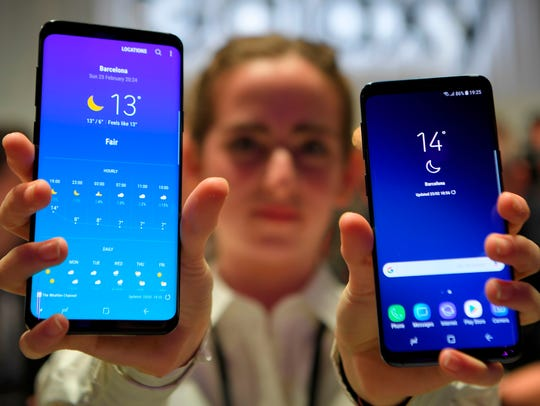 A representative holds two new Samsung Galaxy S9 mobilephones during the Samsung Galaxy S9 Unpacked event on Feb. 25, 2018 in Barcelona.