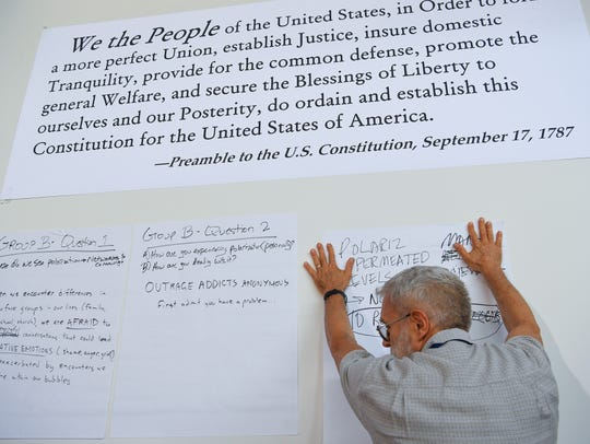 A member of the Better Angels leans on a wall with messages from participants during the group's national convention in early June at Eastern Mennonite University in Harrisonburg, Va.