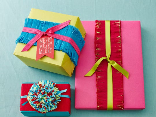 """In this photo provided by Better Homes and Gardens, for gifts that need to be shipped or stacked flat, add a fringed """"belly band"""" around the midsection: Cut a strip of crepe paper long enough to fit the package (either lengthwise or widthwise), fold it lengthwise and cut slits along the edges to fringe. Attach to package and top with a coordinating color of ribbon."""