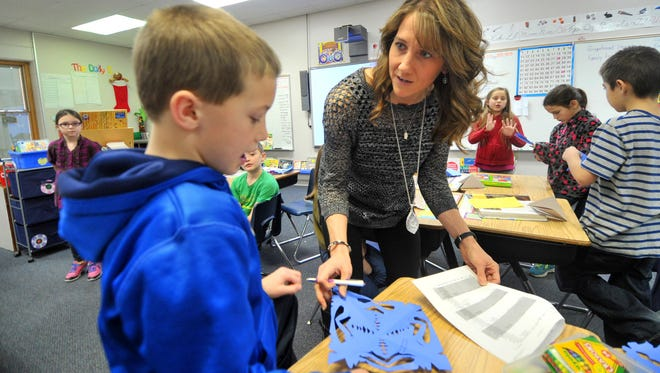 Second grade teacher Peggy Empey works with student Trevor Trowbridge on a paper snowflake at Auburndale Elementary School in this 2015 file photo.