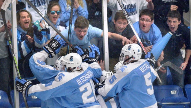 """Livonia Stevenson hockey players celebrate a goal with members of the school's """"Blue Crew"""" cheering section."""