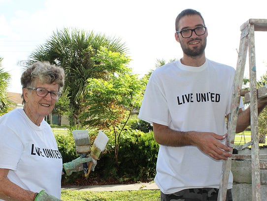 Pat Warner, left, and Will Grimison paint the exterior