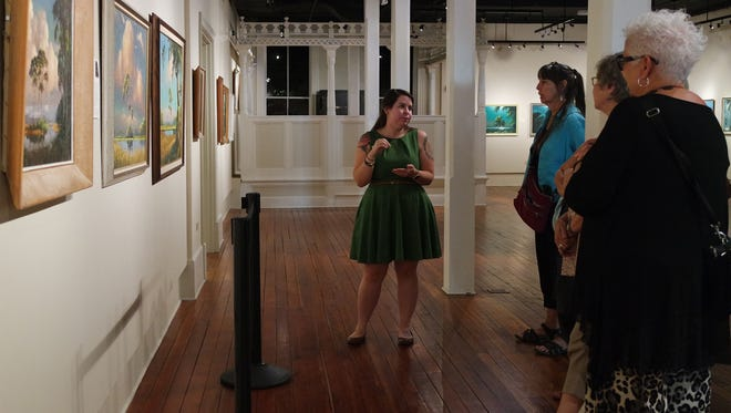 Education Director Anissa Ford talks with a visiting group about paintings by A.E. Backus during a guided tour of the Florida's First Highwaymen exhibition.