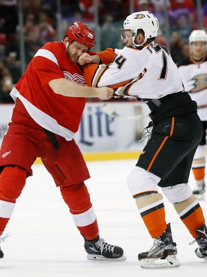 Red Wings center Steve Ott, left, and Ducks left wing Joseph Cramarossa (74) fight in the first period Saturday at Joe Louis Arena.