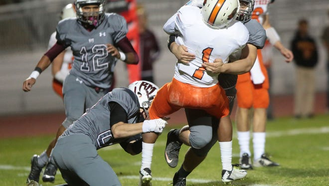 Rancho Mirage's Bryce Wilson-Higgins tackles Polytechnic's Christian Henderson on Friday in Rancho Mirage.
