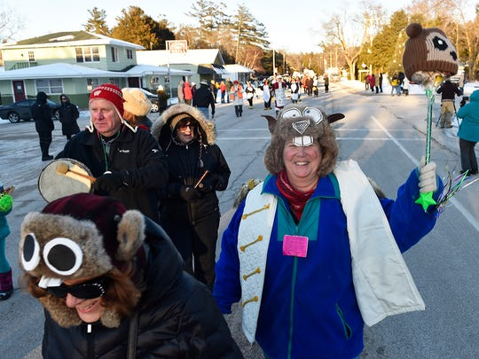 Jerri Lee O'Malley of Baileys Harbor waves her groundhog pole while marching in the Groundhog Day parade in Ellison Bay.