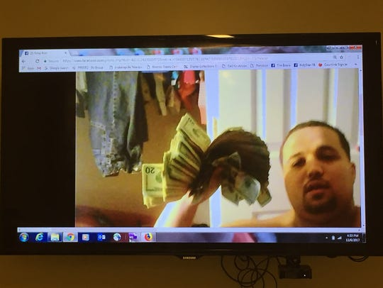 "Richard Grundy III flashes a large wad of cash in this photo posted on his Facebook page. Grundy, a convicted drug dealer, claimed it was one day's take and taunted ""suckas catch up."""