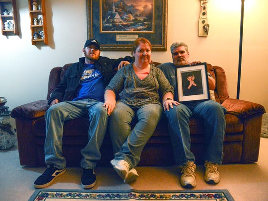 From left, Jonathan Beltz, Tammy Proenneke and Jon Proenneke pose for a photograph in their Ottumwa home with a picture of Joseph Proenneke. Joseph, Tammy and Jon's foster son and Jonathan's foster brother, was killed in a fire in June 2016 in Los Angeles.