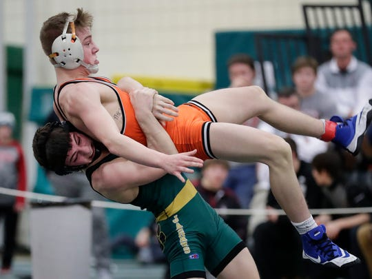 Ashwaubenon's Connor Ramage lifts and slams Brandon Micksch of Kaukauna to the mat during the WIAA Division 1 wrestling sectional meet Saturday at Preble High School in Green Bay. Ramage was penalized for the move.